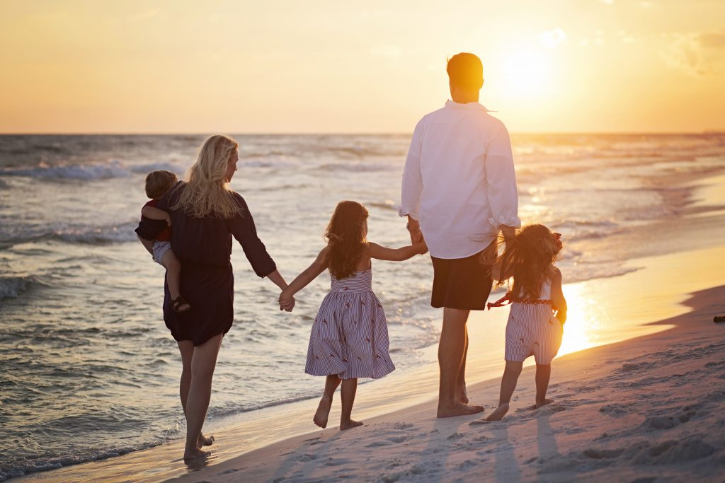 Family walking down the beach in Bay St. Louis, Mississippi.