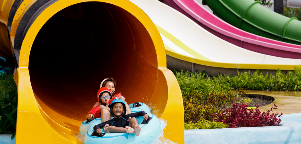 Young children riding a slide at an amusement park in Gulfport, Mississippi.